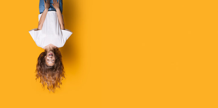 Upside down photo of a caucasian woman in white shirt and jeans smiling on a yellow studio wall with free space
