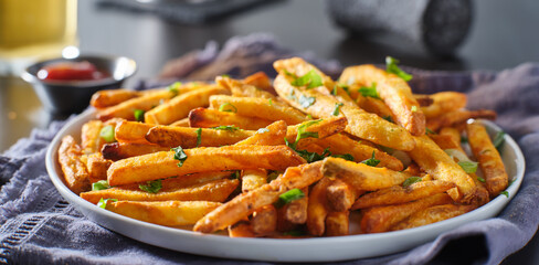 plate of crispy seasoned french fries with parsley garnish