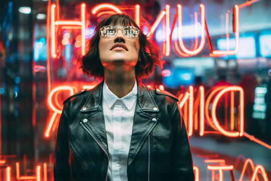 Stylish brunette woman in trendy apparel and eyewear looking up enjoying nightlife in city.Gorgeous hipster girl dressed in leather jacket standing outdoors on street with neon city illumination