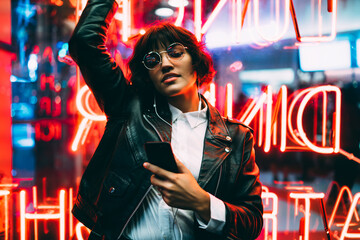 Beautiful brunette woman in trendy apparel and eyewear enjoying nightlife in city listening music in earphones and moving to sound, gorgeous hipster girl dancing outdoors on neon city illumination .