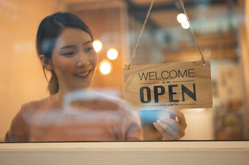 Asian woman store owner turning hanging OPEN sign in front door of her shop