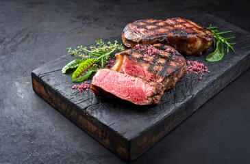 Barbecue dry aged wagyu roast beef steak with lettuce and herbs as closeup on a rustic charred wooden board
