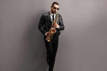 Man in a leather jacket playing a saxophone and leaning on a gray wall Wall mural