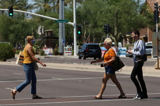 People cross the street between Kierland Commons and Scottsdale Quarter with and without face coverings, during the global outbreak of the coronavirus disease (COVID-19), in Scottsdale