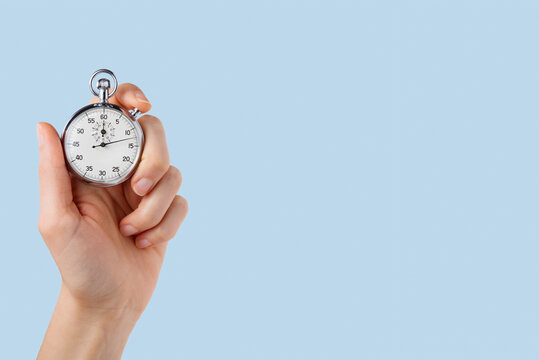 stopwatch hold in hand, button pressed,lighr blue background