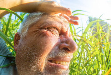 Portrait of an older man. He sweats in the sun and high temperatures in nature.