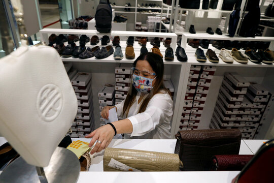 A retail assistant arranges bags in protective face shield as she prepares to open a shop in Singapore as the city state reopens the economy amid the coronavirus disease (COVID-19) outbreak