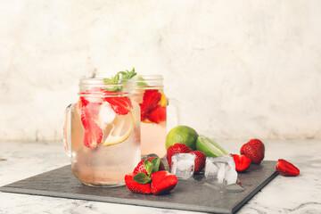 Mason jars of fresh strawberry lemonade on table