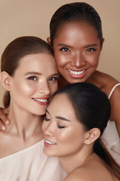 Diversity. Beauty Portrait Of Women. Multi-Ethnic Models With Natural Makeup And Perfect Skin Against Beige Background. Asian, Mixed Race And Caucasian Girls Standing Together And Looking At Camera.