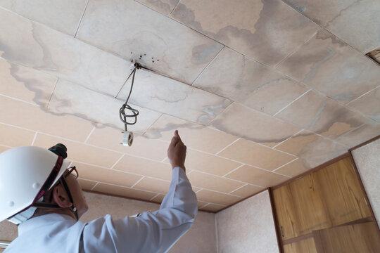 雨漏りした天井を調査するビジネスマン 住宅 リフォーム 解体前