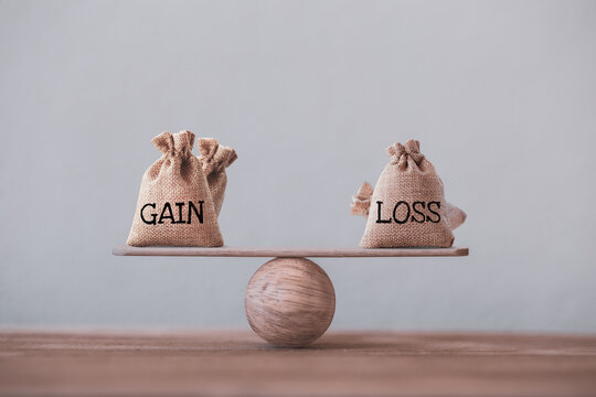 Gain and loss bags on a basic balance scale on table. Capital investment gain and loss, financial concept, depicts balancing between profit and loss while managing assets e.g bonds, stocks, derivative