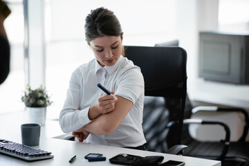 Businesswoman giving herself an injection of insulin.