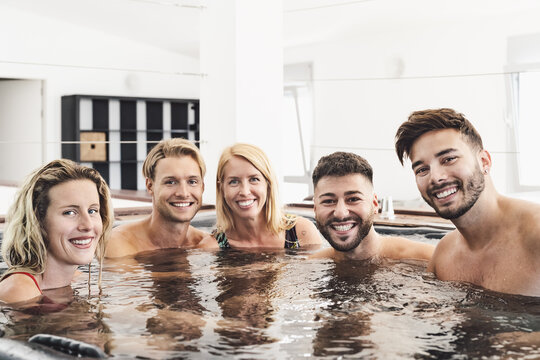 Happy friends enjoying vacations in jacuzzi luxury house - Young people having fun together in hot tub - Youth millennial generation and wellness lifestyle holidays