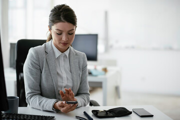 Beautiful businesswoman using digital glucometer in office. Young woman checking blood sugar level