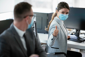 Beautiful businesswoman showing thumbs up. Young businesswoman with medical mask.