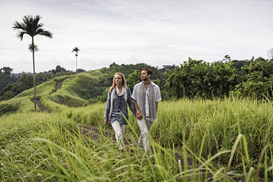 Asia, Indonesia, Bali, young Caucasian couple, wearing smart casual clothing, enjoying a walk along the famous Campuan ridge, one of the well known tourist attractions in Ubud.