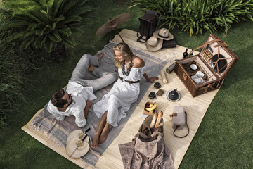 Asia, Indonesia, Bali, young Caucasian couple enjoying a luxury, authentic picnic, set in a tropical garden, , wearing smart casual clothing, while on holiday. Wall mural