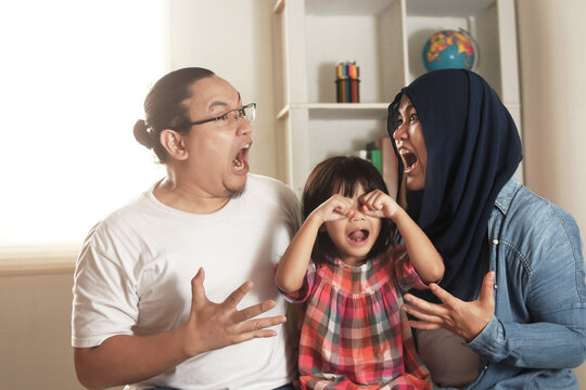 Frustrated little girl daughter scared with mom and dad fighting at home, Asian muslim parents conflict screaming each other makes their baby cries, divorced broken family kid trauma