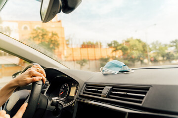 Surgical mask on the dashboard of a car in motion