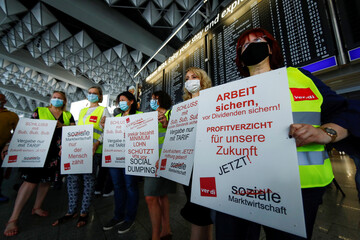 Airport employees and German trade union Verdi members hold placards as they take part in a protest against the reduction of the number of jobs due to the outbreak of the coronavirus disease (COVID-19), at the airport in Frankfurt
