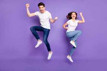 Aluminium Prints Equestrian Full length photo pretty lady handsome guy couple jumping high up raise fists sporty competitions supporters fans wear casual t-shirts jeans pants shoes isolated purple color background