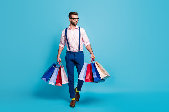 Full body photo of handsome business man worker carry many bags buy clothes vacation shopping center wear specs shirt suspenders pants boots socks isolated pastel blue color background