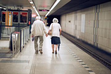 elderly couple holding hands in subway, walking