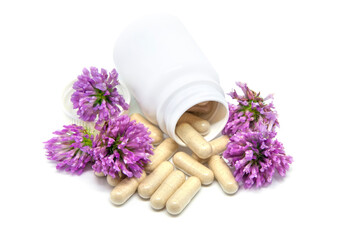 Herbs capsules from clover in white jar with clover flowers