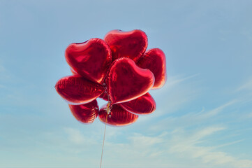 Red heart-shaped balloons with blue sky background in vintage style, concept of love in summer and valentine, wedding