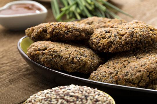 Gluten free and vegetarian quinoa hamburgers on a wooden table.