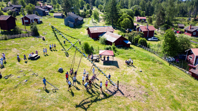 People raise maypole as they celebrate midsummer in a smaller group than usually as the elderly in the village stay at homes or keep distance due to the coronavirus disease (COVID-19) pandemic in Sahl