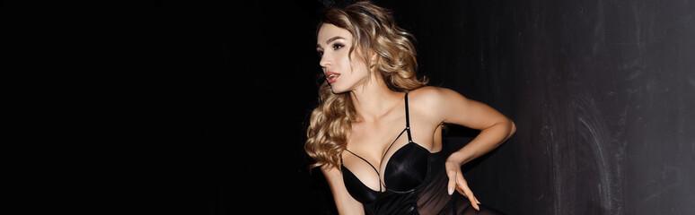 Panoramic crop of beautiful woman looking away near wall on black background
