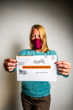woman with mask holding mail in ballot