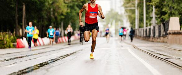 Wall Mural - leader marathon race athlete runner run in rain on city street