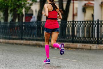 Fotomurales - girl runner in compression socks run in rain marathon on city street
