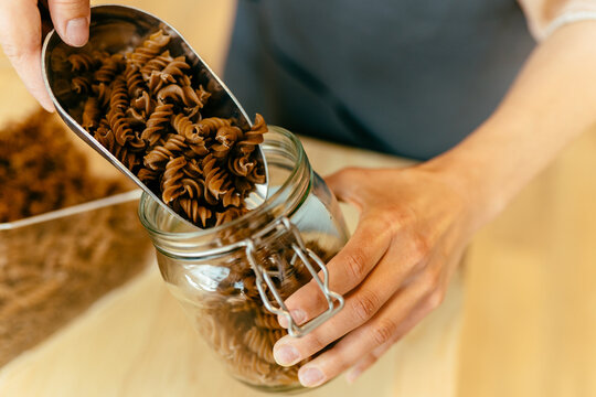 Dark brown whole grains of pasta are poured in glass jar. Close up of unrecognizable woman is pouring pasta to a jar from bulk dry food dispensers at zero waste shop, defocused.