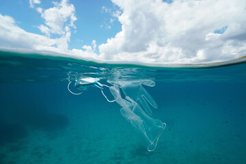 Plastic waste pollution in the sea since coronavirus COVID-19 pandemic, face mask with gloves underwater and sky with cloud, split view over and under water surface