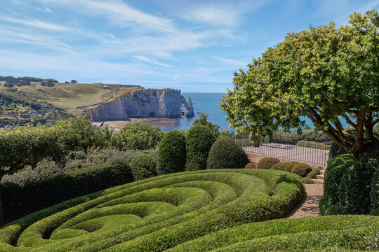Panoramic view of Etretat coastline with white chalk cliffs, Aiguille d'Etretat, natural stone arch from the upper gardens. Etretat, Normandy, France.