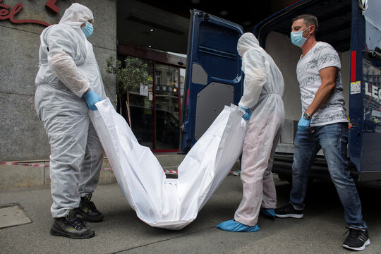 Forensic medicine staff carry a body bag, allegedly containing the remains of Gholamreza Mansouri, outside a hotel in downtown Bucharest