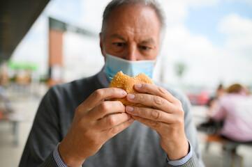Mature man trying to eat a hamburger wearing a mask, funny coronavirus concept