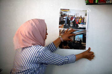 Hadia Ahmad, a Syrian refugee who has recovered from cancer, hangs pictures of her Arabic online classes at home, following the outbreak of the coronavirus disease (COVID-19), in Qushtapa camp, in Erbil