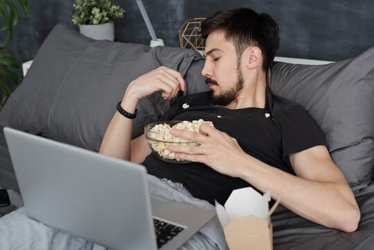 Young man having got popcorn all over him lying with laptop on bed and eating popcorn from tshirt