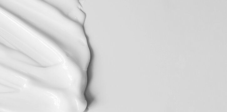 Close-up cream moisturiser smear smudge wavy texture on white background with copy space horizontal banner format. Skin care beauty product