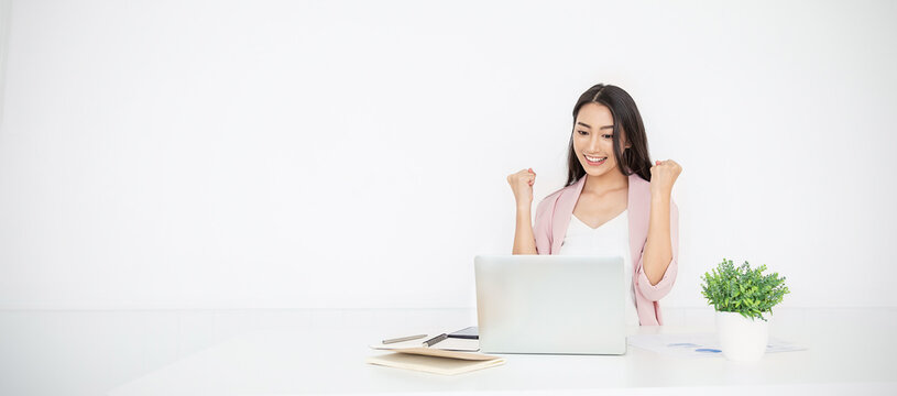 Portrait of smiling beautiful business asian woman with pink suit working in office desk using computer. Small business people employee freelance online sme marketing  telemarketing successful banner