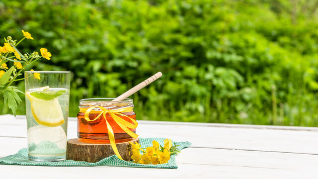 A jar of honey and a glass of lemonade on a hot summer day against a background of green greenery with space to copy.