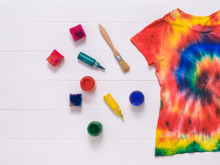 Brushes, paint, and a tie dye t-shirt on white boards. Flat lay. Fotobehang