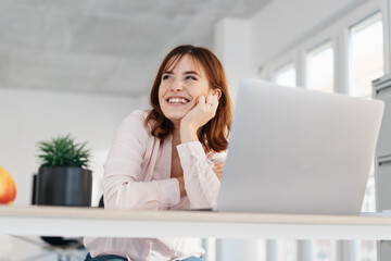 Happy young office employee seated at her desk