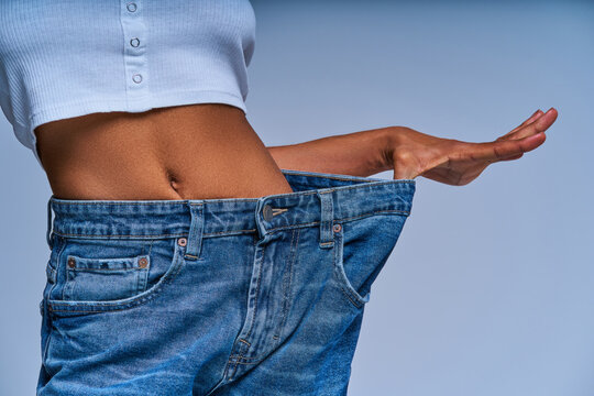 Girl in jeans several sizes larger than she wears shows her belly. Diet concept
