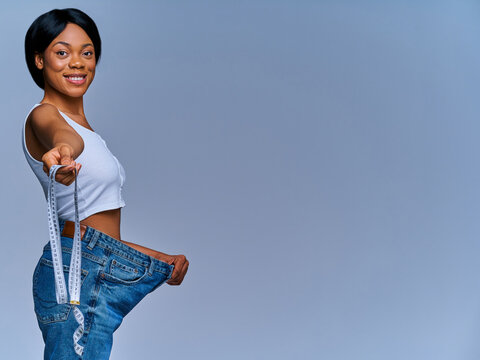 Happy woman in white top in oversize jeans holds out a centimeter tape. Diet concept