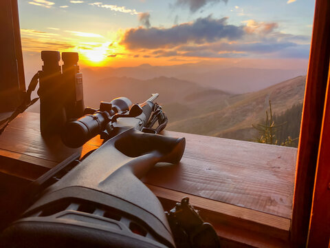 Close up of rifle and binocular for  hunting. View from the window on sunrise.